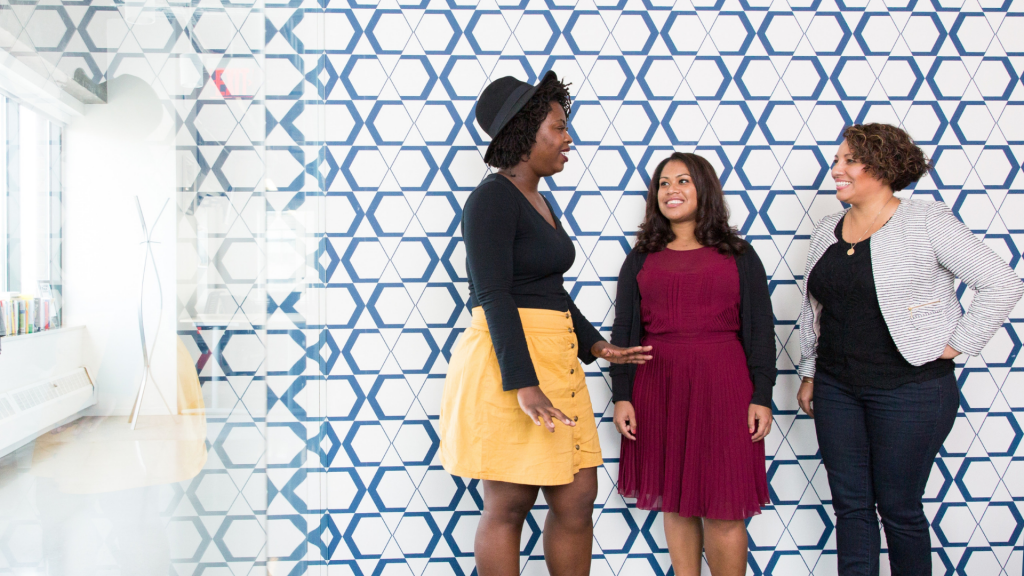 three diverse women talking together in an office