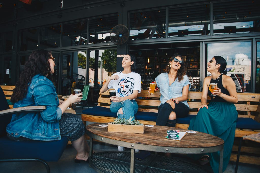 four women gathered around a table enjoying various beverages from a bar or coffee shop