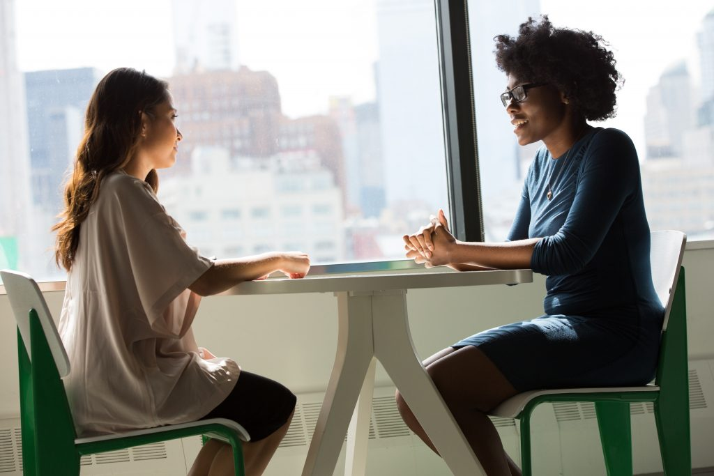 two women engaged in a friendly conversation while seated at a desk in an office