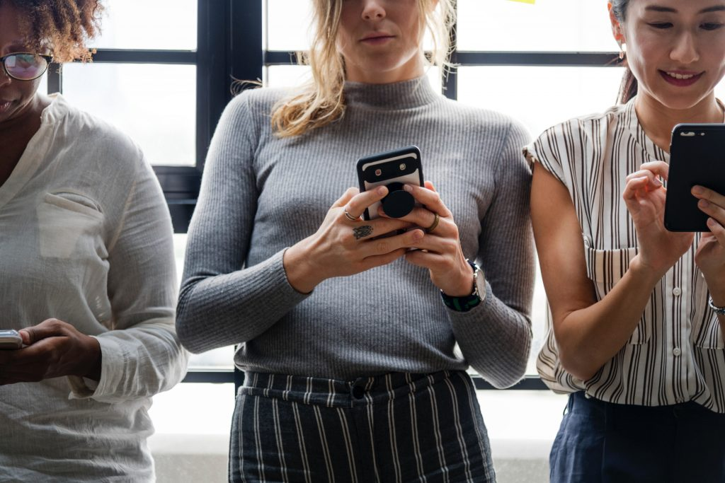 three women standing side by side viewing their cell phones